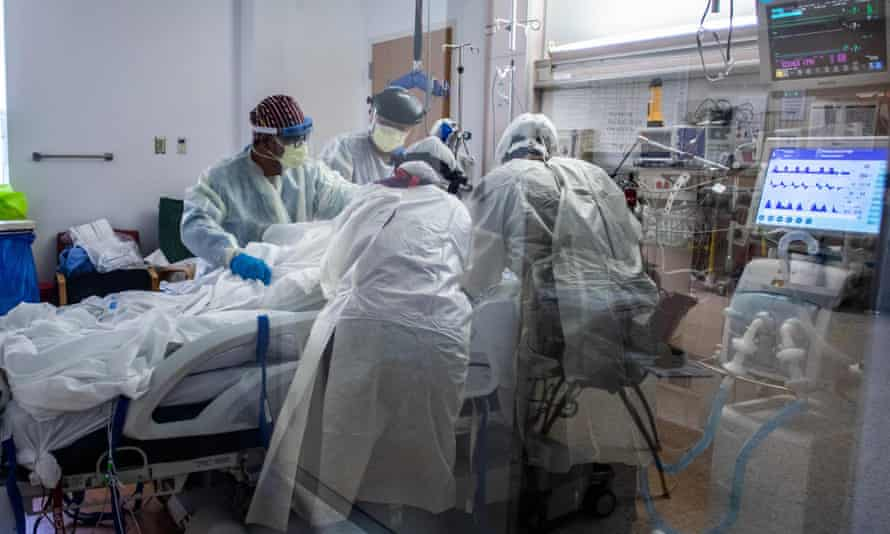 A team of health care workers attend to a patient in the Covid-19 Intensive Care Unit at a hospital in Tarzana, California.