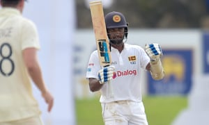 Dinesh Chandimal raises his bat after reaching fifty.