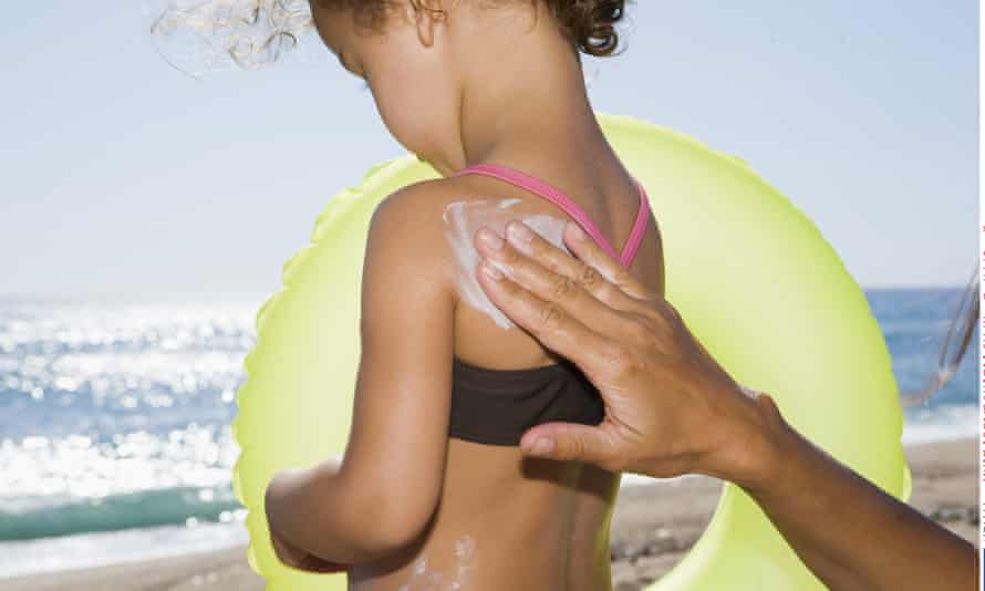 Parent applying sunscreen to child's back