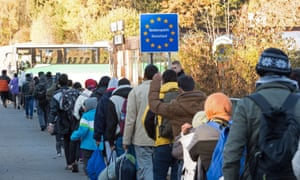 refugees cross the border from Germany into Austria to bord a bus