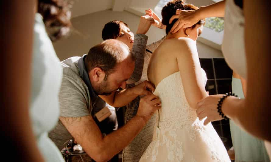 Ibrahim Halil Dudu fixing the zip on Jo Du's wedding dress. The Syrian tailor and his family were being hosted by neighbour David Hobson and had only moved in four days previously.