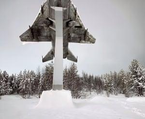 A Soviet-era interceptor is lit by the glow of Murmansk's streetlights
