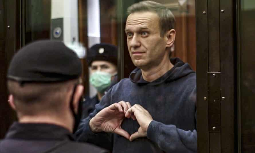 Alexei Navalny makes a heart gesture standing in a cage during a court hearing in Moscow earlier this month