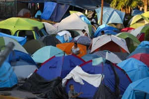 People wake up at a camp near a legal port of entry bridge in Matamoros, Mexico