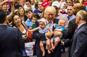 Republican presidential candidate Donald Trump holds baby cousins Evelyn Kate Keane and Kellen Campbell