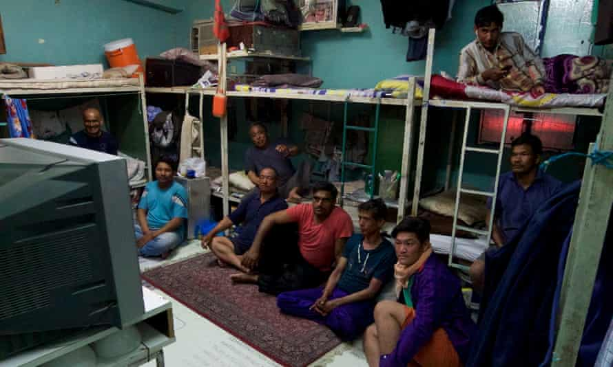 Migrant workers watch television in a labour camp in Qatar.