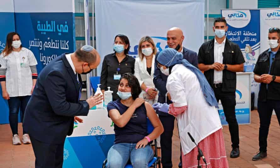 Israeli prime minister Naftali Bennett and a woman getting a vaccine jab