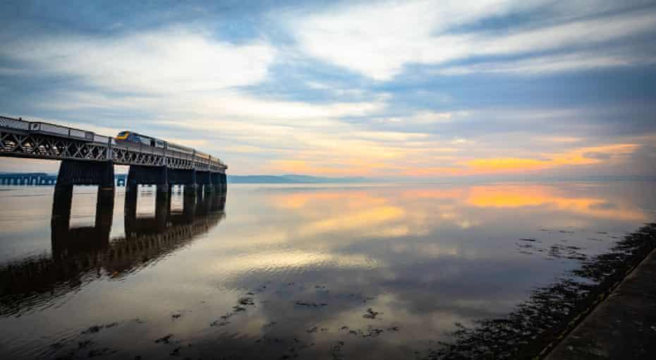 Train crossing a calm Tay estuary at sunset, Dundee, Scotland, United Kingdom.