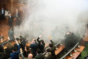 Members of Kosovo's parliament try to proceed with the first parliamentary session of the year despite teargas being released by opposition lawmakers in Pristina