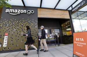 People walk past an Amazon Go store, currently open only to Amazon employees, in Seattle. Amazon Go shops are convenience stores that don't use cashiers or checkout lines, but use a tracking system that of sensors, algorithms, and cameras to determine what a customer has bought.