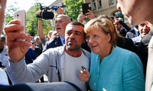 A migrant takes a selfie with German chancellor Angela Merkel outside a refugee camp in Berlin.