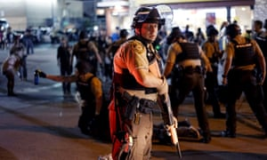 A police officer holds his weapon as a protester is detained in Ferguson, Missouri.