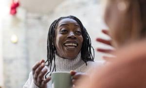A woman with dreadlocks drinking coffee.