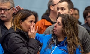 Two GM workers react at a union meeting near the General Motors' assembly plant in Oshawa in Ontario.