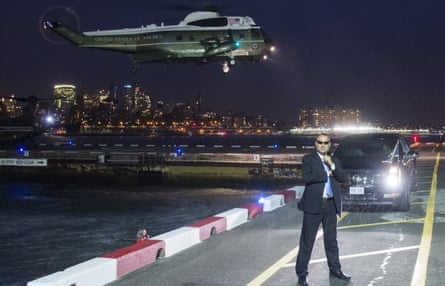 A Secret Service agent stands guard as a helicopter carrying Barack Obama prepares to land in New York