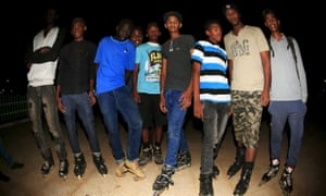 A group of young men take a break from roller blading at a public garden in Khartoum, Sudan