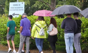 Parents and their children queue in the pouring rain outside the Citywest vaccination centre in Dublin