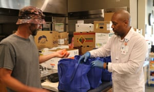 Two people packing food for distribution