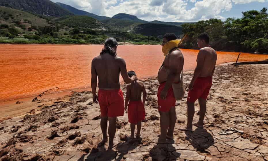 Members of the Krenak tribe look at the Doce river, one month after the Fundão dam disaster in 2015.