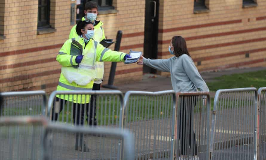 NHS staff hand out test kits to Glasgow University students at a test centre at the Murano Street student village