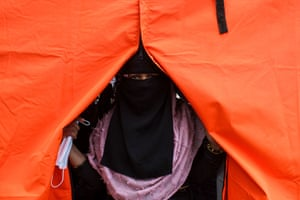 A Rohingya refugee looks out of an orange tent providing temporary shelter