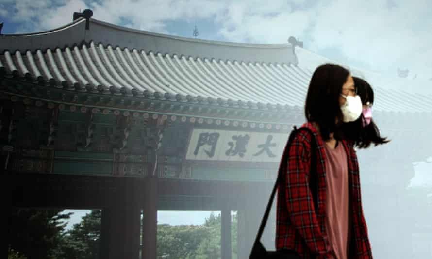 Los peatones que usan máscaras faciales como precaución contra el coronavirus pasan frente a una pared con imágenes del Palacio Deoksugung en Seúl, Corea del Sur, el 7 de julio de 2021.