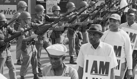 "National Guard troops stand with bayonets fixed as African-American sanitation workers march wearing placards reading ""I AM A MAN."""