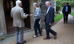 Theresa May and her husband (right) are welcomed at their church, Maidenhead, 26 August 2018.