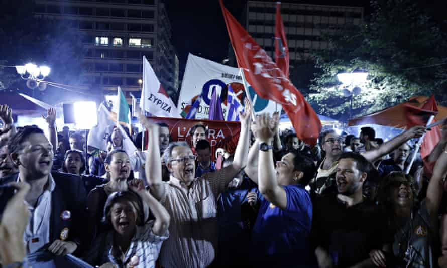 No vote supporters hold a banner during celebrations in Athens as results begin to indicate a clear victory against eurozone austerity measures