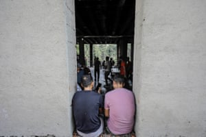 Migrants eat in a burned out building as they wait to pass to European countries in Bihac, Bosnia and Herzegovina