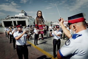 The Municipal Band of Piraeus serenade Little Amal, a giant puppet depicting a young Syrian refugee girl, as she leaves the port of Piraeus in Greece bound for Italy.
