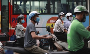 People wear face masks in hopes of curbing the spread of the coronavirus riding mopeds in Hanoi. Vietnamese health official said on Thursday the Covid-19 outbreak would peak in the coming ten days as the country reported another death and a score of new infections.