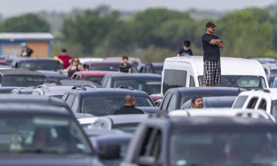 People wait for the San Antonio Food Bank to begin food distribution as need soars.