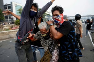 Demonstrators protect an elderly woman during  clashes with police in Jakarta, Indonesia