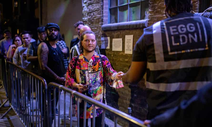 Young people queueing to get into a nightclub in London