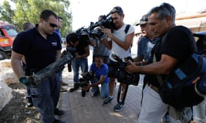 An Israeli police officer shows journalists part of the rocket which was launched from Gaza into Sderot.