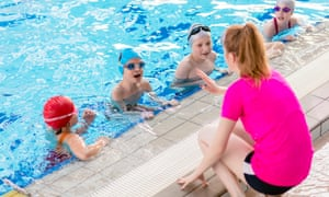 happy children at group swimming lesson