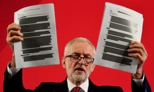 Jeremy Corbyn holds up a report