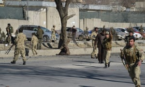 Afghan security personnel gather at the site of a suicide bomb next to a police base in Kabul.