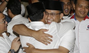 Anies Baswedan, centre right, hugs his running mate Sandiaga Uno after winning the election.