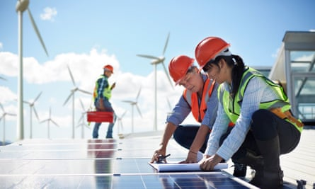 Engineers reviewing blueprints at solar panel at power plant