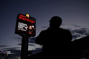 """A man looks at a sign at a strip club advertising """"coronavirus-free lap dances"""" Friday, March 13, 2020, in Las Vegas."""