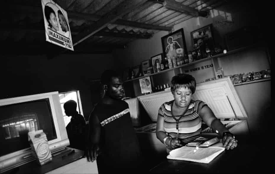 A woman sits at a desk in a Zambian border town