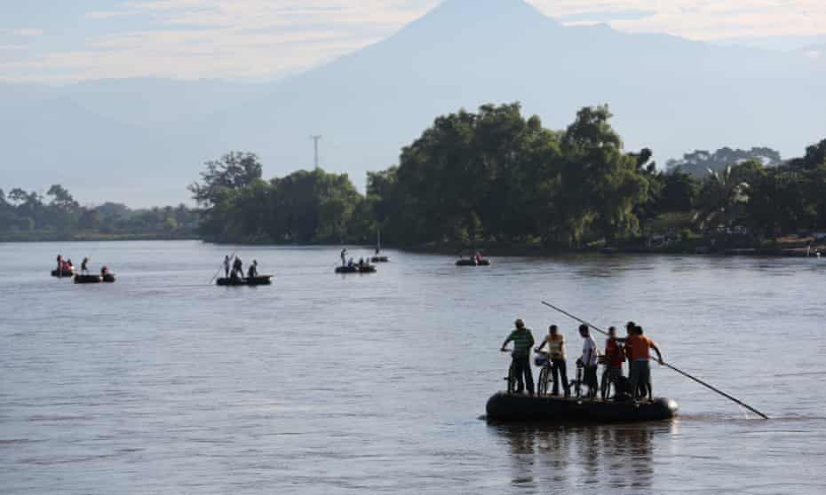 People cross the Suchiate River on rafts from Guatemala into Mexico. Thousands of undocumented Central Americans pass illegally through Mexico on their way to the United States.