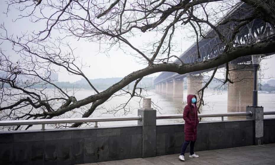 A woman walks under the Yangtze River Bridge in Wuhan