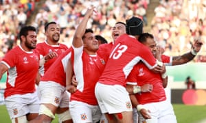 Telusa Veainu is mobbed after scoring Tonga's fourth try in the last minute of the match, denying USA a losing bonus point.
