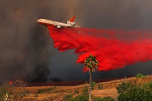 A DC-10 aircraft drops fire retardant on a wind driven wildfire in Orange