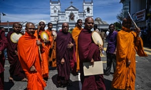 Buddhist monks outside St Anthony's Shrine in Colombo, a day after the church was hit in series of bomb blasts.