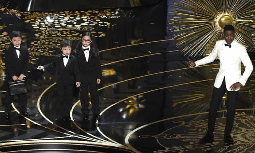 Chris Rock, right, gestures to three children in a skit at the Academy Awards 2016