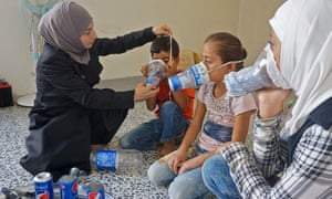 Um Majid, left, tries an improvised gas mask on familiy members in her home in Binnish in Syria's rebel-held northern Idlib province as part of preparations for expected attacks by government forces and their allies.